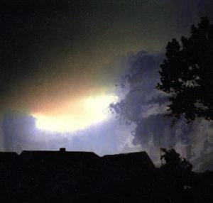 Die Silhouette eines Daches, vor dem Hintergrund eines dunklen Himmels, durch das ein helles Licht scheint.